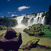Argentina, Igwazu, Igwazu Falls. Salto San Martin thunders into the river below as a boat full of adventure seekers heads for the pool.