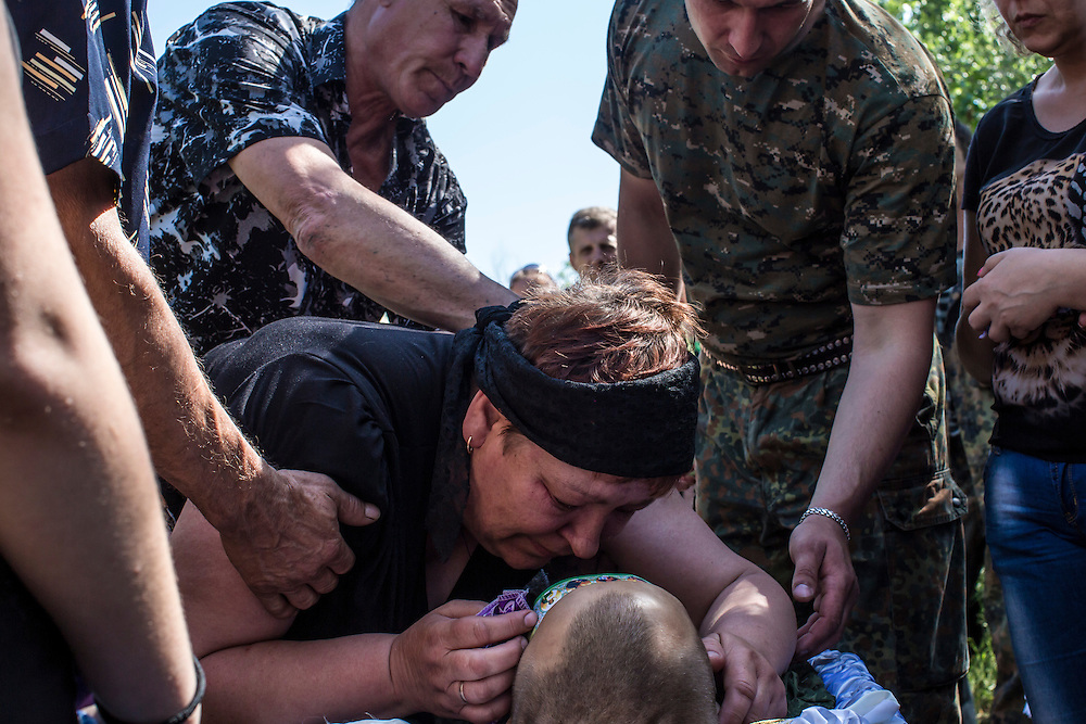 HORLIVKA, UKRAINE - MAY 24: Relatives grieve over the body of Aleksandr Politov, a pro-Russia militia fighter who was killed when his group attacked a Ukrainian military checkpoint two days earlier in the village of Blahodatne, on May 24, 2014 in Horlivka, Ukraine. Presidential elections are scheduled for tomorrow, but pro-Russia militias have been seeking to prevent them from being administered throughout the eastern part of the country. (Photo by Brendan Hoffman/Getty Images) *** Local Caption ***