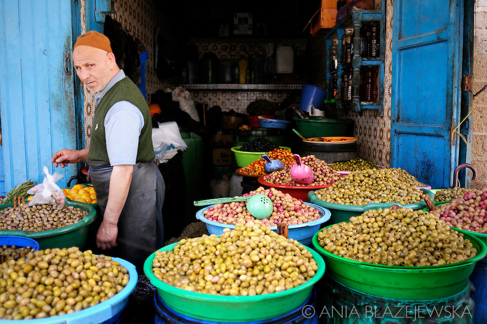 Morocco, Essaouira. Man selling  a huge choice of olives.