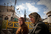 Two Palestinian ladies walk past one of the first checkpoints in Hebron, Palestinian Territories. Image © Angelos Giotopoulos/Falcon Photo Agency