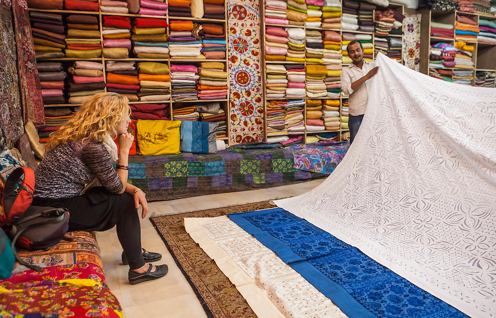 A woman sits and views textiles being shown by a salesman in a show room, Jodhpur, Rajasthan, India.
