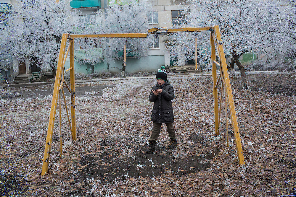 A boy stands under a swingset damaged when a shell landed a few feet away on Saturday, December 12, 2015 in Zolote, Ukraine.