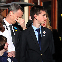 (Boston, MA - 4/15/15) Martin Richard's father Bill wipes his eyes as  siblings Jane and Henry stand together after unveiling banners honoring bombing victims and survivors on Boylston Street at the site of one of the Boston Marathon blasts, which killed Martin two years ago, Wednesday, April 15, 2015. Staff photo by Angela Rowlings.