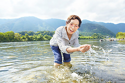 Lifestyle image of happy granny in her 80s in river in Japanese countryside