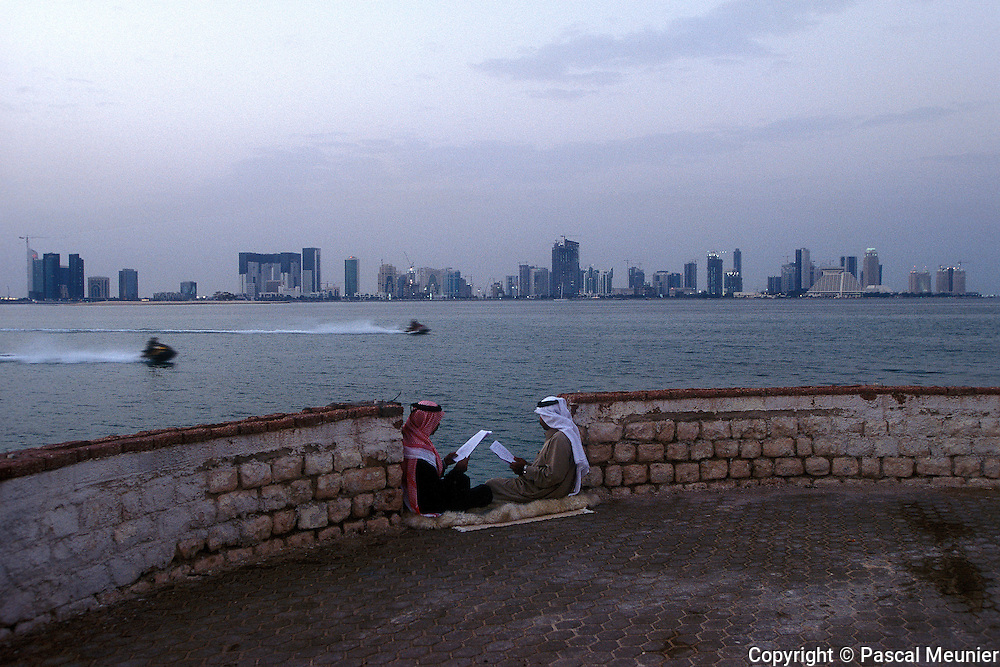 QATAR. Doha. Friends on the Cornice...At sundown, Qataris make way to the Cornice. While some have fun on jet-skis, in fashion in the capital, others study their English courses before the following day exam.