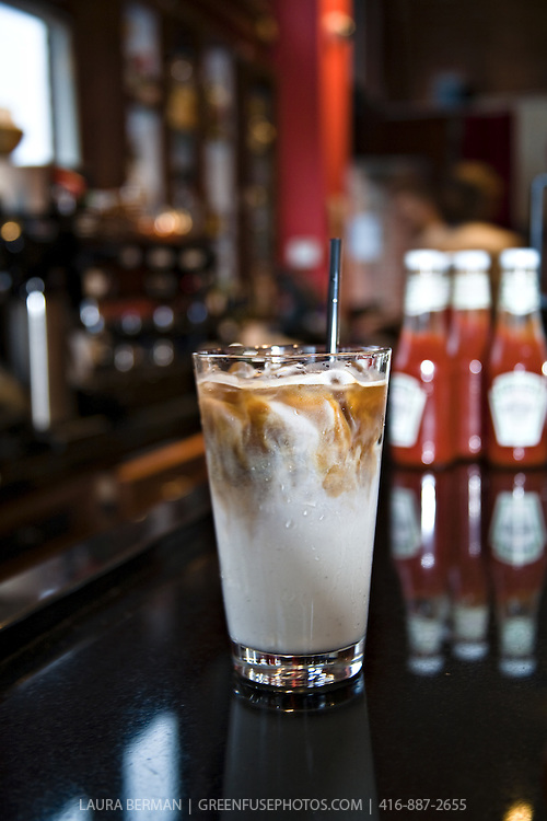 An iced coffee or iced latte in a large glass on a black counter with espresso machine and ketchup bottles in the background.