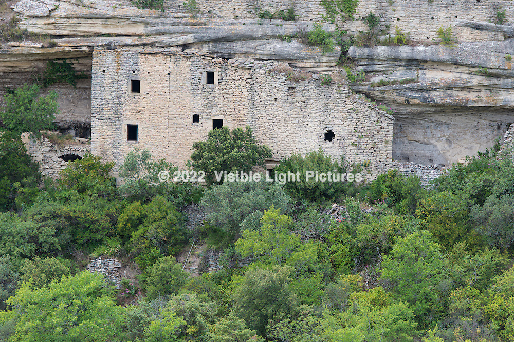 A building in Gordes built into the side of a hill.  This is part of the view from the terrace of a hotel restaurant across the valley.