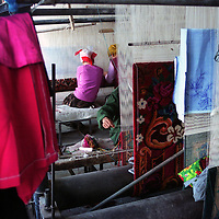 HOTAN,2 OCOTBER 2001: Uighur girls weave carpets in a factory.. Uighur muslims in southern Xinjiang province lead very basic lifestyles and have an average monthly income of about 50 US$.. (photo by: katharina hesse/Grazia Neri).