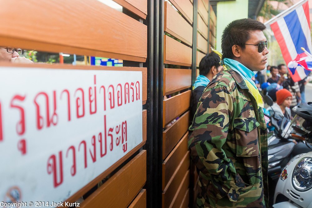 26 JANUARY 2014 - BANGKOK, THAILAND:   An election worker (left) inside a school at Wat That Thong is blocked from getting to the polling place by an anti-government protestor (right). Anti-government protestors forced the closure of polling places in Bangkok Sunday as a part of Shutdown Bangkok. Protestors blocked access to gates and entry ways to polling places and election officials chose the close them rather than confront protestors. Early voting was supposed to be Sunday January 26 but blocked polling places left hundreds of thousands of people unable to vote casting the February 2 general election into doubt and further gridlocking Thai politics. Shutdown Bangkok has been going for 12 days with no resolution in sight. Suthep, the leader of the anti-government protests and the People's Democratic Reform Committee (PDRC), the umbrella organization of the protests,  is still demanding the caretaker government of Prime Minister Yingluck Shinawatra resign, the PM says she won't resign and intends to go ahead with the election.  PHOTO BY JACK KURTZ