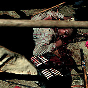 POLITICS CONFLICT SOUTH AFRICA MAR 1994: A member of the Inkatha Freedom party lies dead outside the African National Congress headquarters 'Shell House' March 1994, Johannesburg, South Africa.  There was extensive violence and thousands of deaths in the run-up to the first non-racial elections in South Africa in April 1994. (Photo by Greg Marinovich / Getty Images)