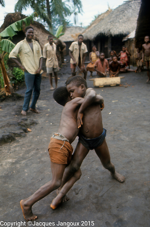 Africa, Democratic Republic of the Congo, Ngiri River area, Libinza tribe. Boys performing traditional Pongo wrestling to the beat of drums.