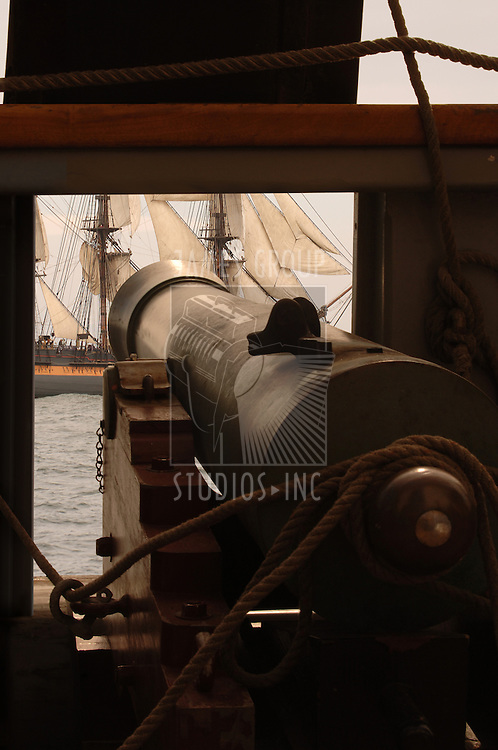 Gun cannon on vintage sailing ship aiming at another sailing vessel