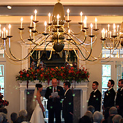 The wedding ceremony is conducted amongst family and friends in a finely decorated room.