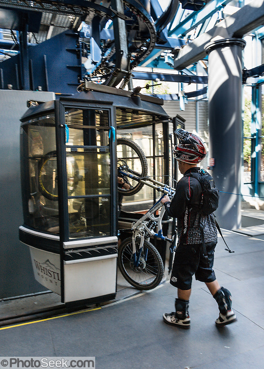 A padded and helmeted mountain biker loads his bicycle onto Whistler Village Gondola in the Fitzsimmons Range, British Columbia, Canada. The Resort Municipality of Whistler is popular for a variety of outdoor sports.