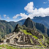 Peru, Morning sun lights Inca ruins at Machu Picchu with Huayna Picchu peak rising above the Urubamba River