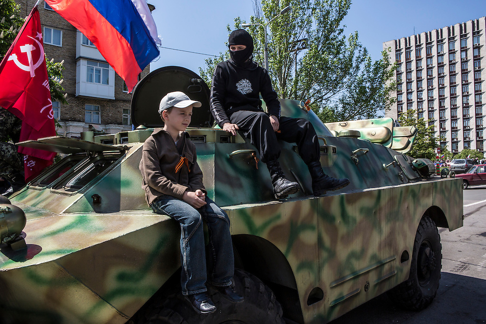 DONETSK, UKRAINE - MAY 10: A boy poses for a photo with pro-Russia activists atop an armored personnel carrier outside the occupied regional administration building on May 10, 2014 in Donetsk, Ukraine. A referendum on greater autonomy is planned for the region tomorrow. (Photo by Brendan Hoffman/Getty Images) *** Local Caption ***