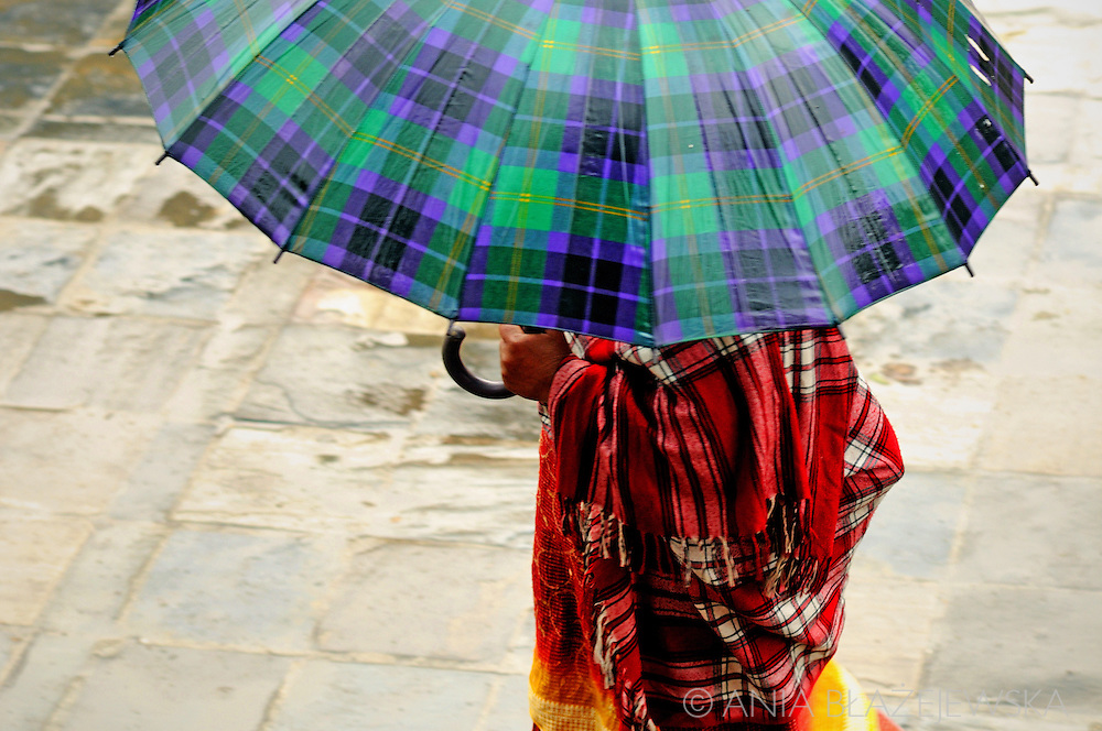 Nepal, Kathmandu. Checkered pattern umbrella and shawl of woman walking the streets during a rainy day.