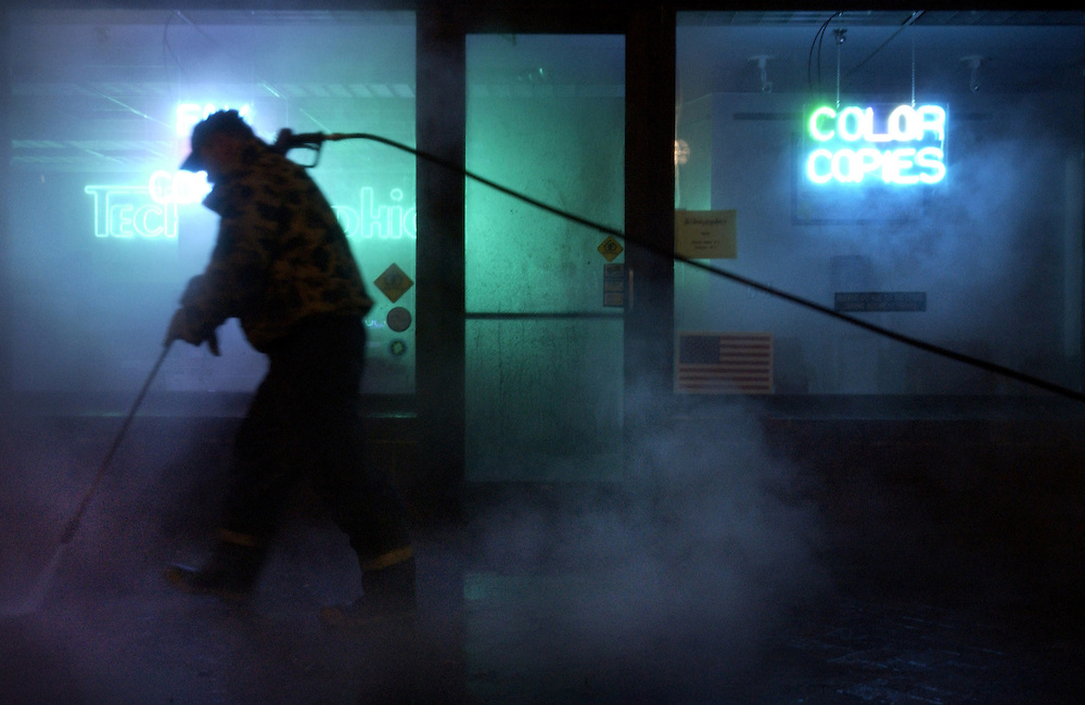 A worker power washes a brick sidewalk early Monday morning April 8, 2002, in front of Technigraphics Printing in the Pedestrian Mall in Iowa City, Iowa. The city has the mall cleaned every year to remove grime built up over the winter. Scott Morgan Photography