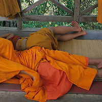Asia, Laos, Luang Prabang, Young Buddhist monks lie in shade during heat of day near Wat Tham Phu Si temple