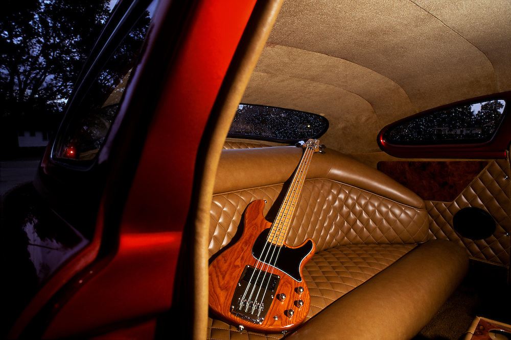 Ibanez stained wood-grained  sexy electric bass guitar tucked into the backseat of a red mint condition low rider with shining tan quilted and tufted leather back seat. Shot in Houston, Texas.