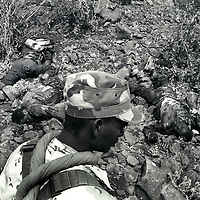 An Eritrean soldier passes some dead Ethiopian soldiers, near Tsorana, Eritrea.