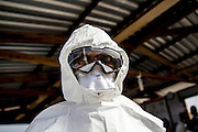Dr Peter Githua puts on his Personal Protective Equipment (PPE) before heading inside the red zone, patient ward. IOM Ebola treatment unit (ETU) in Sinje, Liberia. The ETU brings clinical care closer to Ebola patients in Grand Cape Mount County, where active transmission persists in hotspots such as Tewor, Porkpa and Gola Konneh districts. This treatment facility is one of three USAID-supported Ebola treatment units managed by IOM including others in Tubmanburg, Bomi County and Buchanan, Grand Bassa County.<br /> <br /> The new treatment facility opens with 10 beds and the capacity to rapidly scale up to 50. USAID&rsquo;s Office of U.S Foreign Disaster Assistance is supporting IOM to operate the ETU in partnership with Liberia&rsquo;s Ministry of Health and Social Welfare (MOHSW) as part of the Government of Liberia&rsquo;s Ebola response strategy.<br /> <br /> The treatment unit in Sinje is run by 23 medical professionals from Kenya, South Africa, Tanzania, Uganda and Ukraine. IOM also recruited and trained 114 Liberians from Grand Cape Mount County to offer clinical and non-clinical care within the facility. The staff received training from the World Health Organisation (WHO) and the MOHSW, including hands-on training at the IOM-managed ETU in Tubmanburg, Bomi County.UNMEER/Martine Perret. 27 January 2015