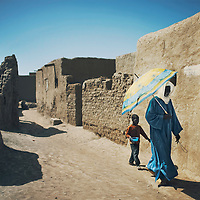 A man and his grandson walk in a narrow street in Djenne, Mali.