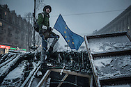 Taras, 18, an anti-government protester stands guard next to an European flag, a symbol of the protest movement, on one of the barricades defending Maidan Square against police and government supporters on December 9, 2013 in Kiev, Ukraine. Thousands of protesters have taken to the streets since Ukrainian president Viktor Yanukovych announced a decision to suspend a trade and partnership agreement with the European Union and raised concerns that the nation could be poised to enter a customs union with Russia.