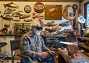 Copper artist Clark Mundy and his work in his Port Angeles WA studio. He is renowned for his sculptures of salmon, native American masks, and sea life, all made from sheet copper. He creates them using a simple array of tools: copper snips, a torch for heating and annealing the metal, copper welding rod, and small tools for hammering the metal into shapes of his design.