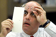 Broward County Canvassing Board member, Judge Robert Rosenberg, stares at a dimpled punchcard ballot November 23, 2000 as the board begins counting the county's ballots that were considered questionable. After review by the three member panel. Photo ©Colin E Braley