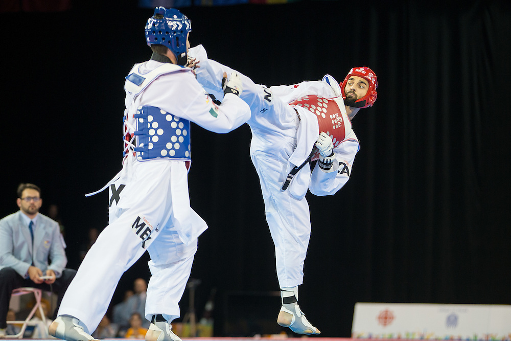 Maxine Potvin (L) of Canada tries to kick Saul Gutierrez of Mexico during their gold medal contest in the men's Taekwondo -68kg division of at the 2015 Pan American Games in Toronto, Canada, July 20,  2015.  AFP PHOTO/GEOFF ROBINS