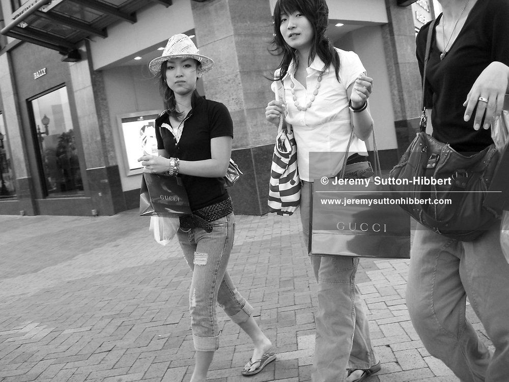 Japanese tourists clutching their Gucci shopping bags in Tumon, Guam, on Saturday, Mar. 10, 2007.  Sometimes known as 'America in Asia', Guam is a popular destination for Japanese tourists ( accounting for approx 90% of the island's visitors) with average visitor numbers from Japan approaching 1million.  The island, a 3.5 hour flight from Japan, has more than 20 large hotels and numerous duty-free shopping malls catering to the Japanese tourists predilection for designer brand name goods, as well as golfing and other water based entertainment features. In 2007-2008 US military personal currently stationed in the Japanese Okinawan Islands will relocate their bases and operations  to Guam, helping to stabilise the island's economy which suffered after tourism decreased in recent years due to a  fear of flying by Japanese post 9-11 World Trade Centre disaster, a 2003 typhoon and the SARS disease outbreak in Asia.