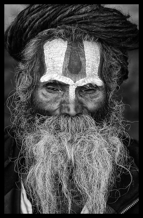 A Katmandu, Nepal Holy man, also know as a Sadhu, looks on from one of the many shrines in the city.
