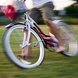A man takes a joyride on a girl's bike and skids to a stop on a summer evening at Sewallcrest Park in Portland, Oregon.