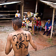 "A Thai man wears writing on his body ""Buffalo"" during festivities at Thailand's Phi Ta Khon Ghost festival Friday, June, 22nd, 2012, in Dan Sai, Thailand.  The Dan Sai Ghost Festival is unique to the Isan area of Thailand in the east and is part of local beliefs in spirits and ghost and is also a Buddhist merit making festival.  The ghost masks are made from bamboo sticky rice cookers and the costumes usually strips of cloth sewn together.  The origins of the Phi Ta Khon Festival are said to come from Buddha's last great incarnation before attaining Enlightenment."
