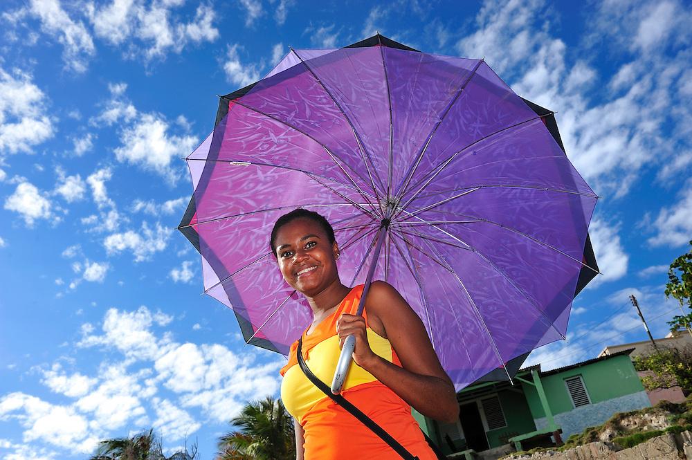 Woman with sun umbrella,Enriquillo,Barahona,Dominican Republic, Caribbean..