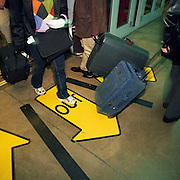 Air passengers exit and enter a transit train at Chicago O'Hare airport, Illinois USA. They pull suitcases behind them as they negotiate the airport terminal transport system that takes them across the sprawling complex of terminals and tunnels. A large central yellow traffic arrow saying OUT is most prominent telling arriving people to keep in the middle, allowing those departing to enter the carriage from the sides. There is a slight blur to the picture showing the hurrying nature of modern air travel, vastly different from the pioneering days of flight for only the socially elite. Picture from the 'Plane Pictures' project, a celebration of aviation aesthetics and flying culture, 100 years after the Wright brothers first 12 seconds/120 feet powered flight at Kitty Hawk,1903..