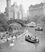 21 Jul 1933, Manhattan, New York, New York, USA --- On the Lake in the Park. Keeping as cool as the hot weather will permit by rowing on Central Park Lake, New York City, in the shadows of the Sherry-Netherlands, Savoy Plaza, and Plaza hotels. --- Image by © Bettmann/CORBIS