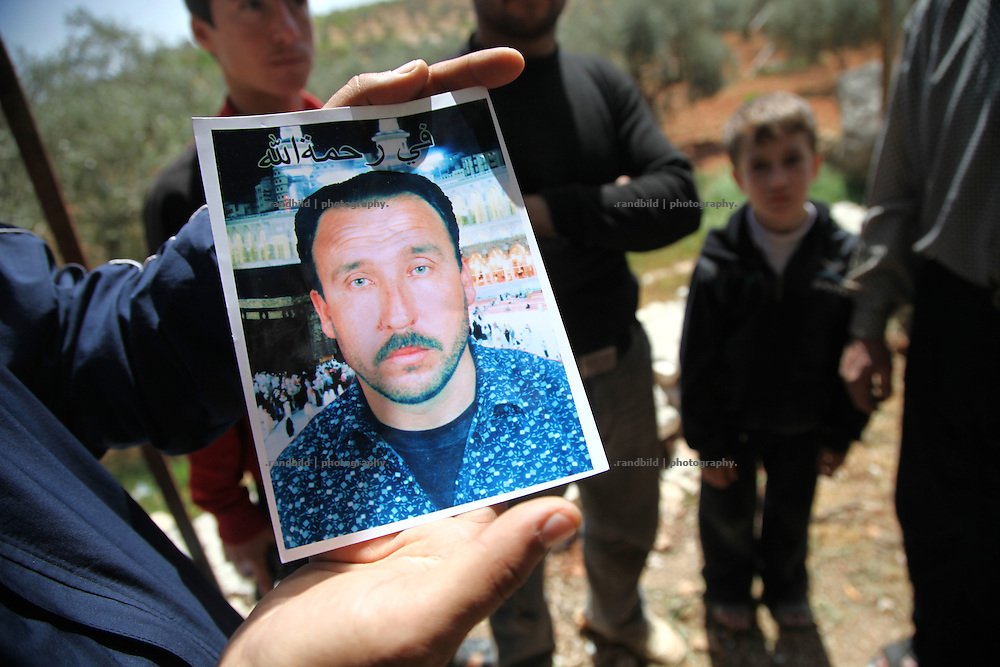 A man shows a portrait of a father killed in Martin during the latest army attack on the village.