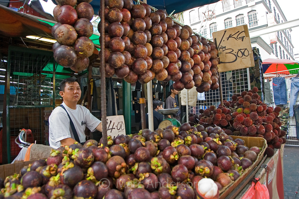 A man selling tropical fruits (mangosteen) at a street stall in Kuala Lumpur, Malaysia.