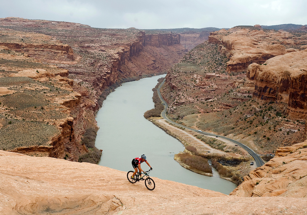 Paul DeWitt rides on a section of slickrock overlooking the Colorado River in Moab, Utah. The well-known Slickrock Trail in the Sand Flats Recreational Area is one of Moab's most popular mountain biking trails. Its steep, technical climbs and super-fast descents make it one of the most challenging trails in the area as well.