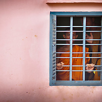 Monks hide behind the barred window.