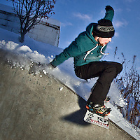 Urban snowboarder, Chris Brewster, performs a Wallie Fronline 270 on the 5th Avenue Hill across from Elderberry Park, downtown Anchorage