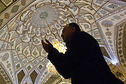 A man prays in the prayer hall of Sayyidah Ruqayya Mosque, a shrine located in Damascus, Syria, that contains the grave of Sukayna (née Ruqayyah), the infant daughter of Husayn ibn 'Alī. Built in 1985 in a modern style of Iranian architecture.