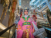 26 JANUARY 2017 - BANGKOK, THAILAND:  Performers ride an escalator during Chinese New Year, also called Tet, celebrations at Emporium, a high end shopping mall in Bangkok. 2017 is the Year of the Rooster in the Chinese zodiac. This year's Lunar New Year festivities in Bangkok were toned down because many people are still mourning the death Bhumibol Adulyadej, the Late King of Thailand, who died on Oct 13, 2016. Chinese New Year is widely celebrated in Thailand, because ethnic Chinese are about 15% of the Thai population.      PHOTO BY JACK KURTZ