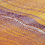 The standstone in a wash in the Valley of Fire State Park, Nevada shows colorful streaked patterns. This wash is comprised of several different layers of sandstone, which have been exposed through erosion.