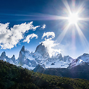 """Sun with lens flares over Mount Fitz Roy (3405 meters or 11,170 feet) in the southern Andes mountains, near El Chaltén village, in Los Glaciares National Park, Argentina, South America. Bright sun creates lens flares shining through a stopped down camera aperture. In 1877, explorer Perito Moreno named """"Cerro Fitz Roy"""" for Robert FitzRoy (no space before the capital R) who, as captain of the HMS Beagle, had travelled up the Santa Cruz River in 1834 and charted much of the Patagonian coast. First climbed in 1952 by French alpinists Lionel Terray and Guido Magnone, Mount Fitz Roy has very fickle weather and is one of the world's most challenging technical ascents. It is also called Cerro Chaltén, Cerro Fitz Roy, and Monte Fitz Roy (with a space before the R). Chaltén comes from a Tehuelche (Aonikenk) word meaning """"smoking mountain"""" (explained by frequent orographic clouds). Cerro is a Spanish word meaning hill. El Chaltén village was built in 1985 by Argentina to help secure the disputed border with Chile, and now tourism supports it, 220 km north of the larger town of El Calafate. The foot of South America is known as Patagonia, a name derived from coastal giants, Patagão or Patagoni, who were reported by Magellan's 1520s voyage circumnavigating the world and were actually Tehuelche native people who averaged 25 cm (or 10 inches) taller than the Spaniards. Mount Fitz Roy is the basis for the Patagonia company's clothing logo, after Yvon Chouinard's ascent and subsequent film in 1968."""