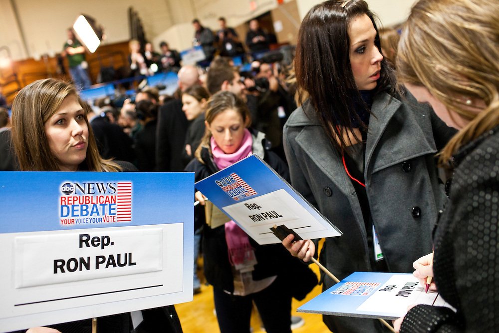 People hold signs for Republican presidential candidate Ron Paul in the spin room following the WMUR/ABC News Debate at Saint Anselm College on Saturday, January 7, 2012 in Manchester, NH. Brendan Hoffman for the New York Times