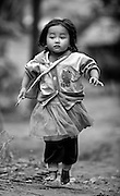 A girl appears to be floating as she runs near her Luang Namtha village in Laos.