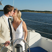 A kiss bride and groom on sailboat ride.